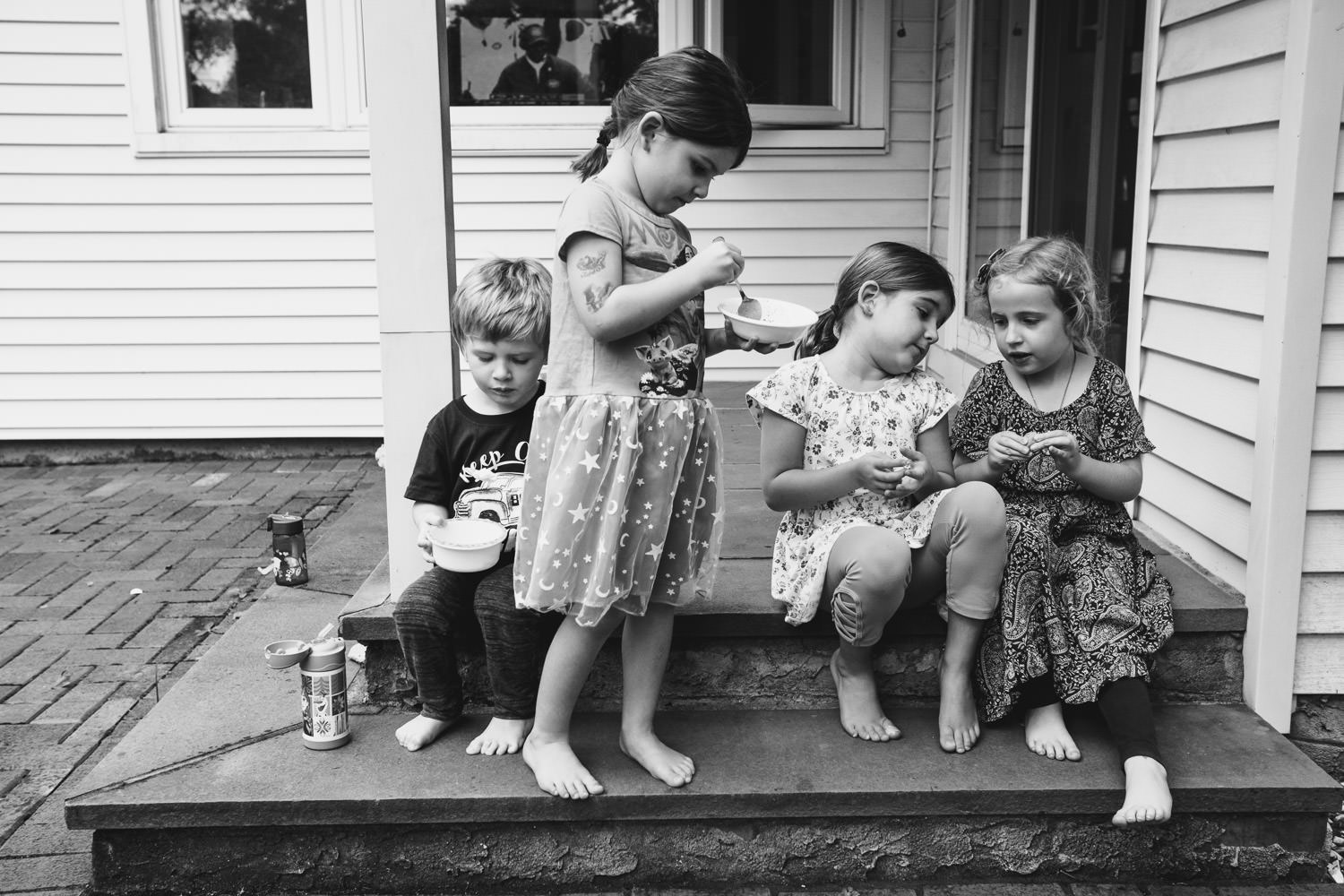 Kids sit and eat their ice cream on the front porch.