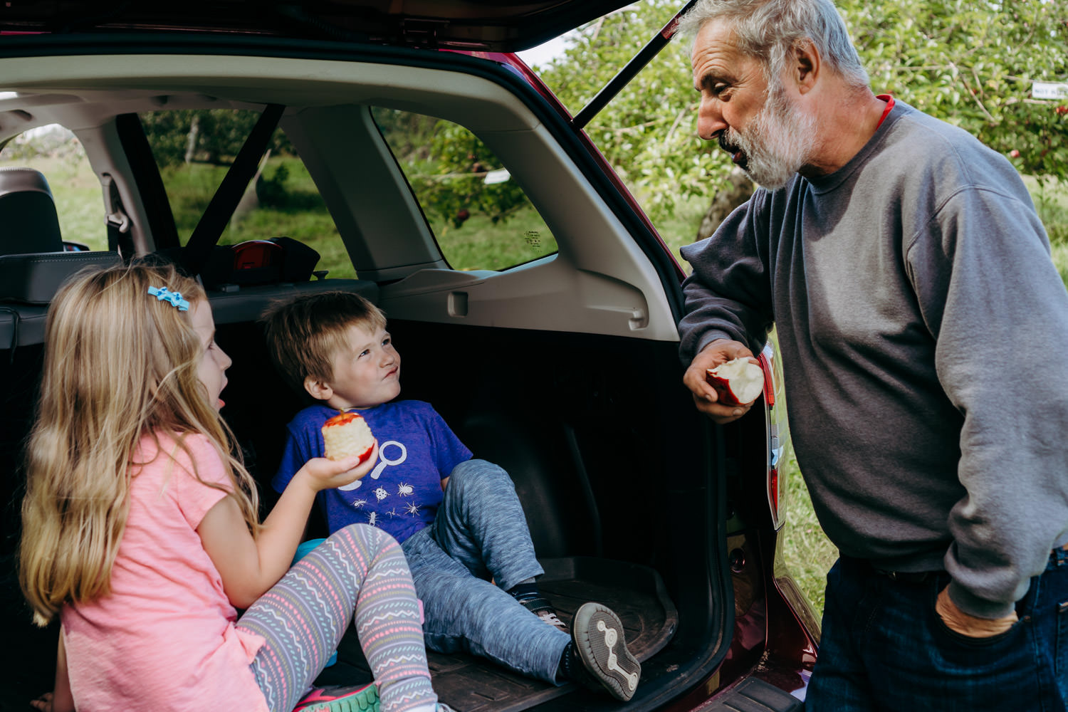 Two children sit in the back of a car and talk to their grandfather.