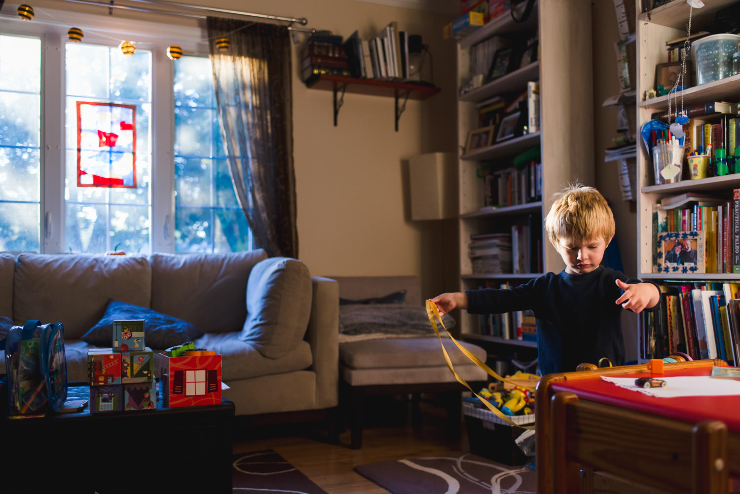 A little boy plays with some ribbon in his living room.