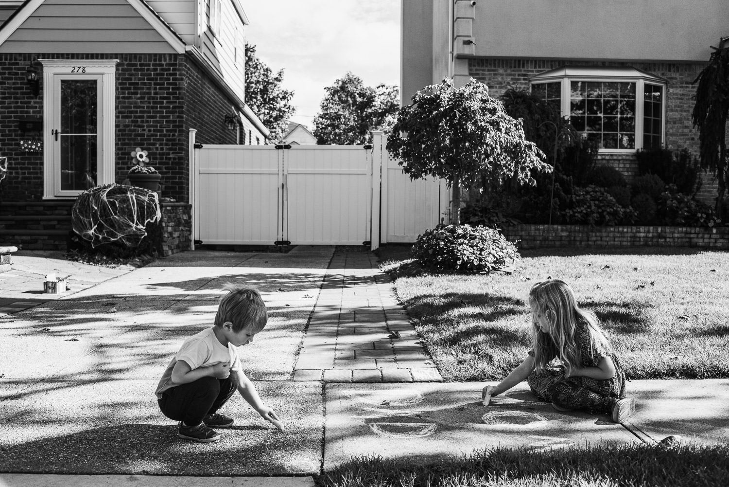 A boy and girl draw with chalk in their driveway.