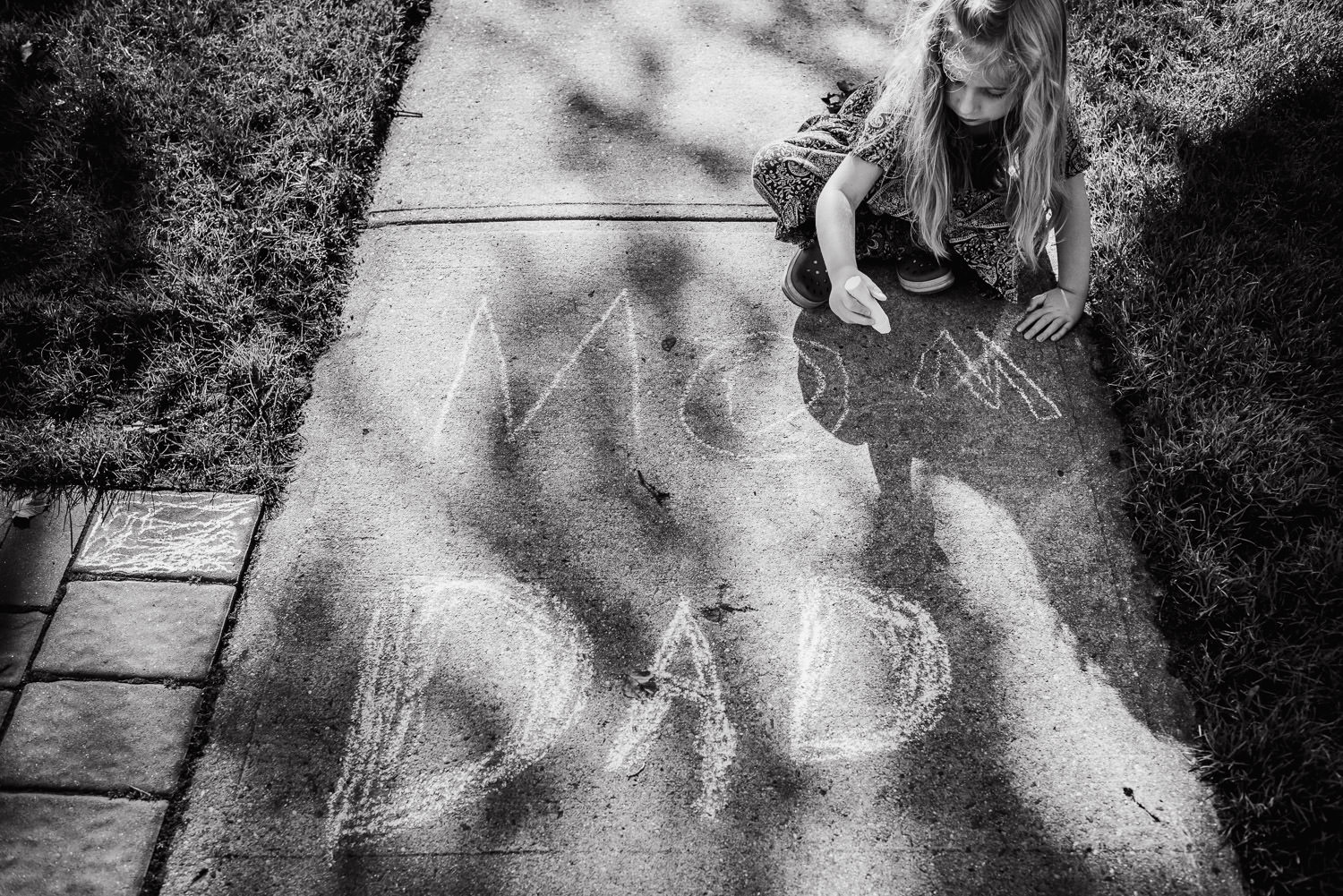 A little girl draws with chalk.