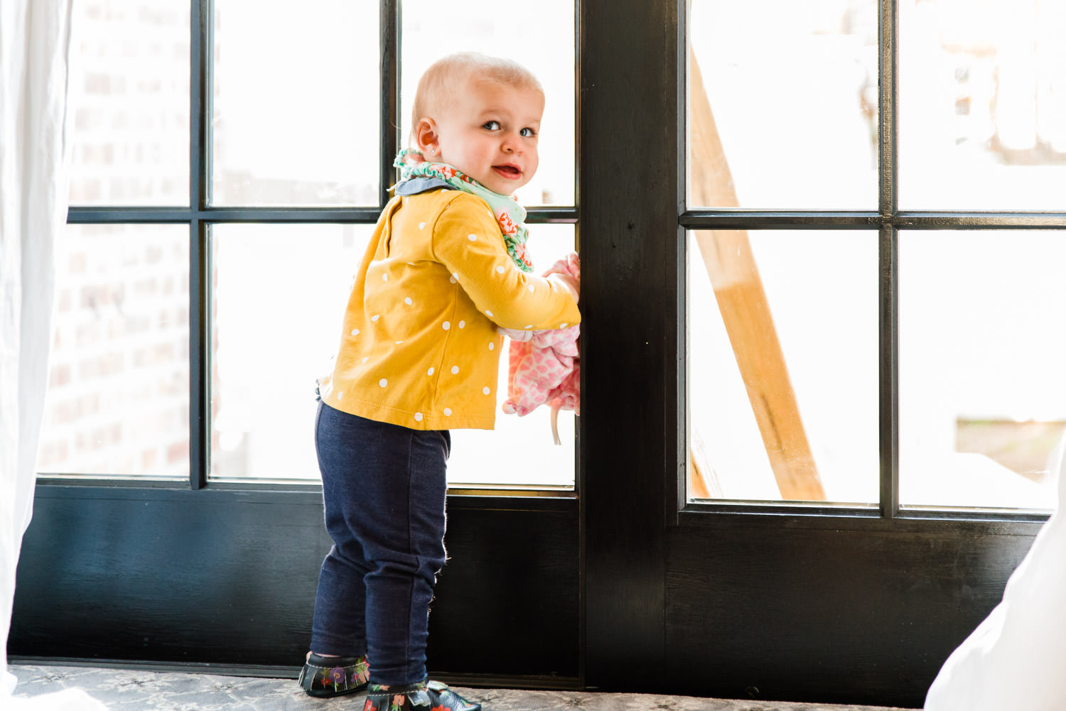 A toddler girl looks out a sliding glass door.