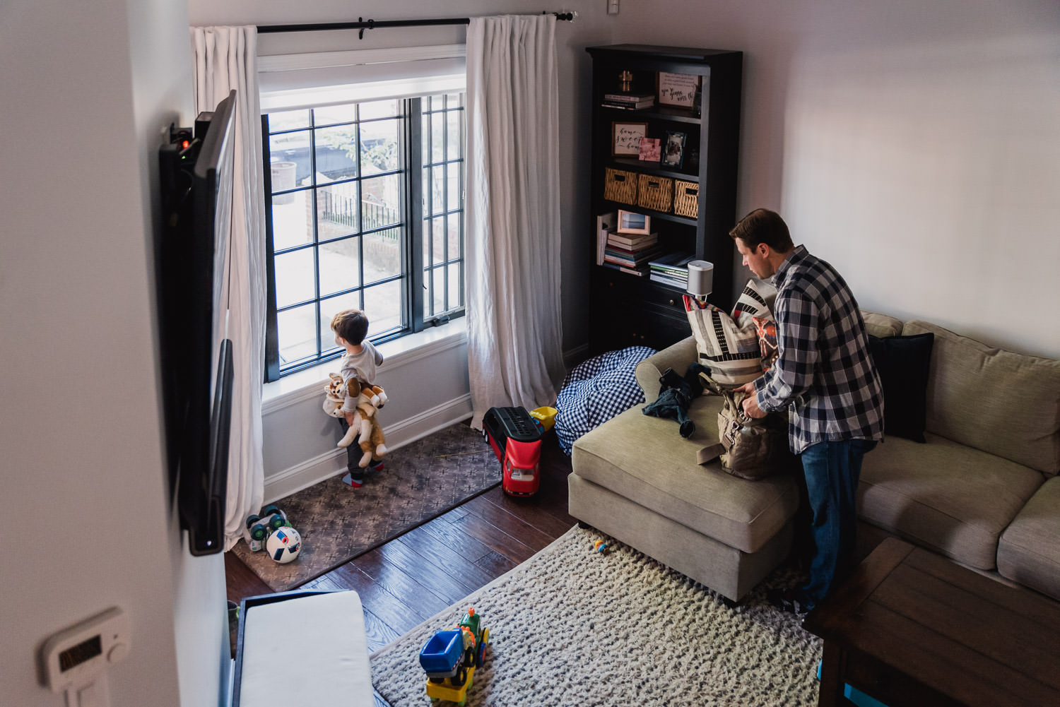A boy and his father look out a large living room window.