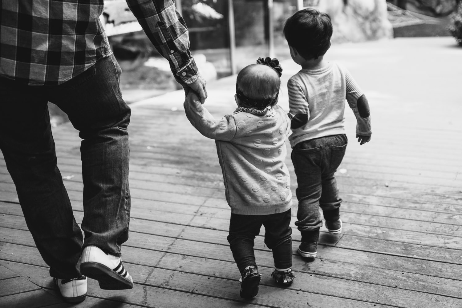 Children hold hands with their father at the Bronx Zoo.