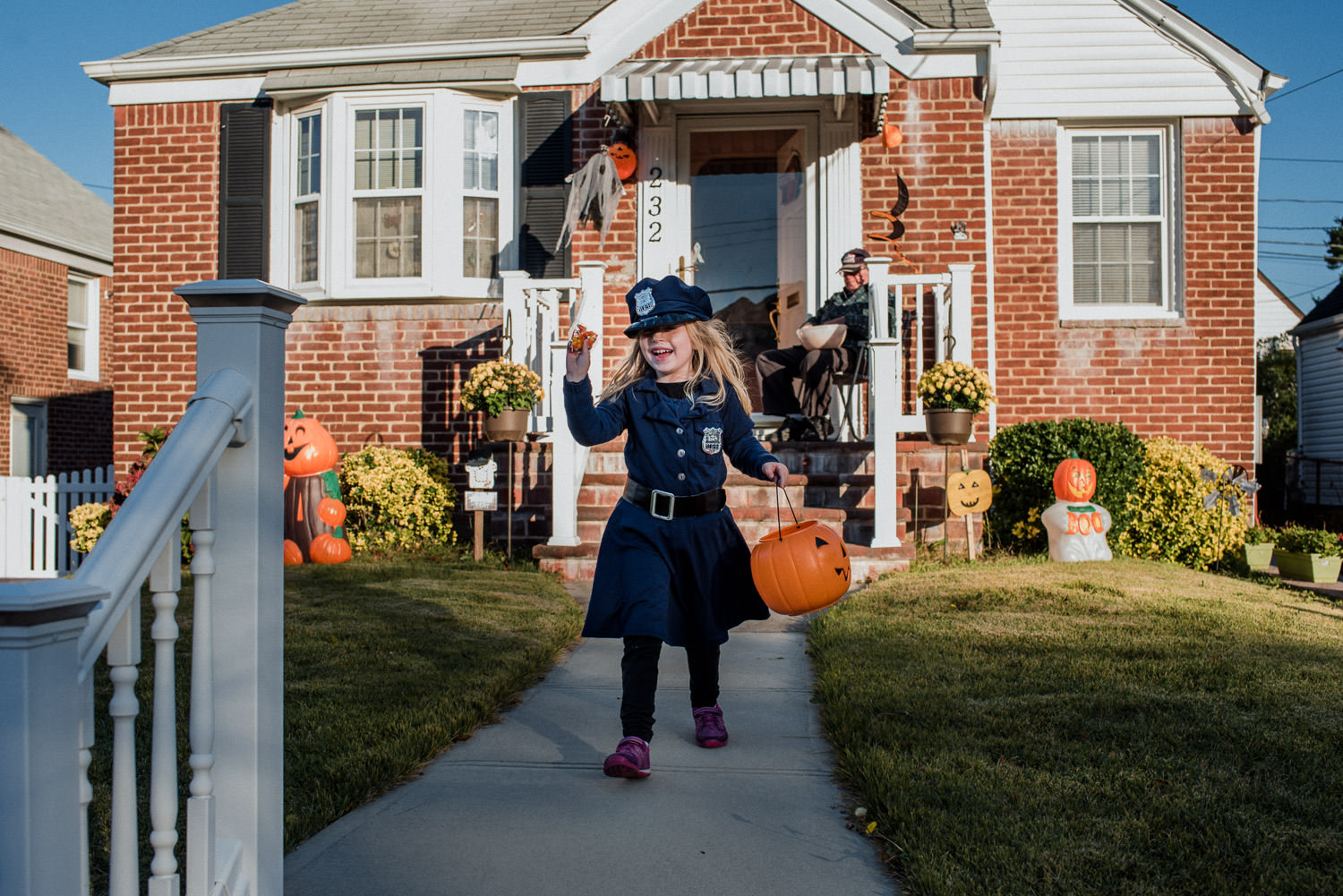 A little girl dressed as a police officer trick or treats.