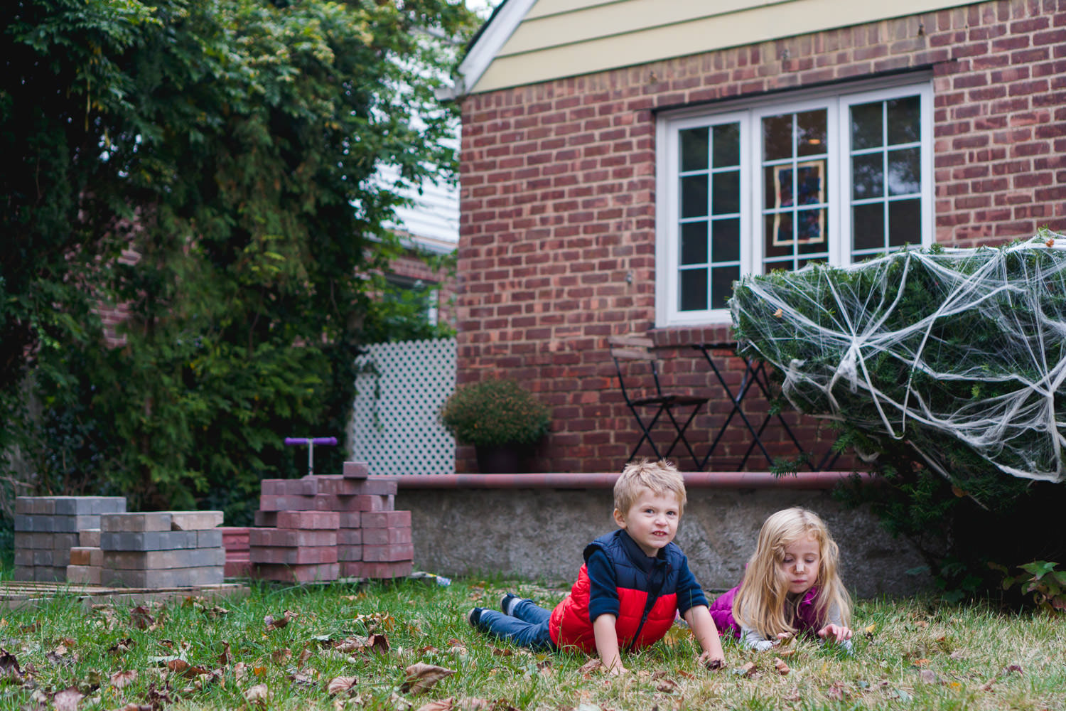 Two kids lie on their front lawn with a pile of bricks behind them.