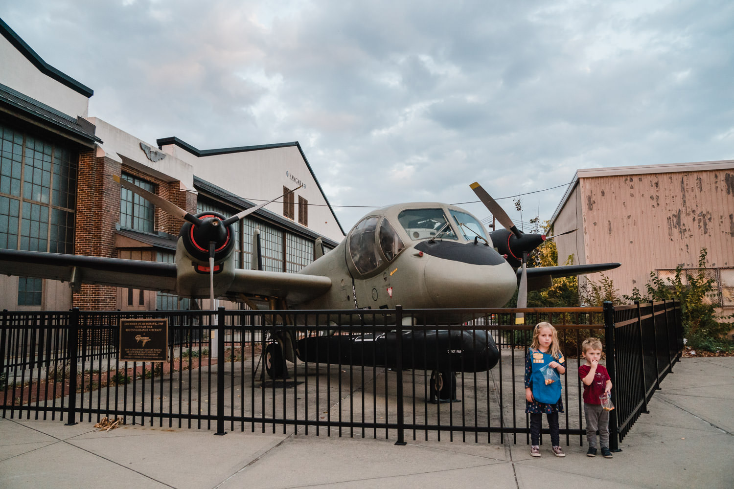 Two children stand in front of an airplane outside the Cradle of Aviation.