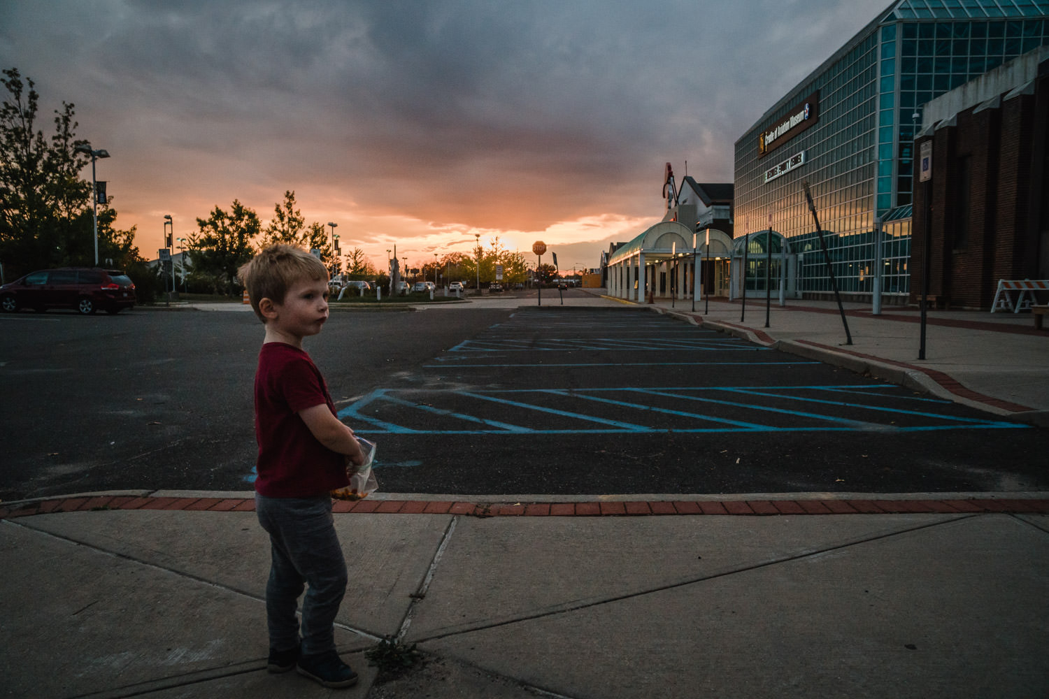 A little boy stands in front of a sunset outside the Cradle of Aviation.