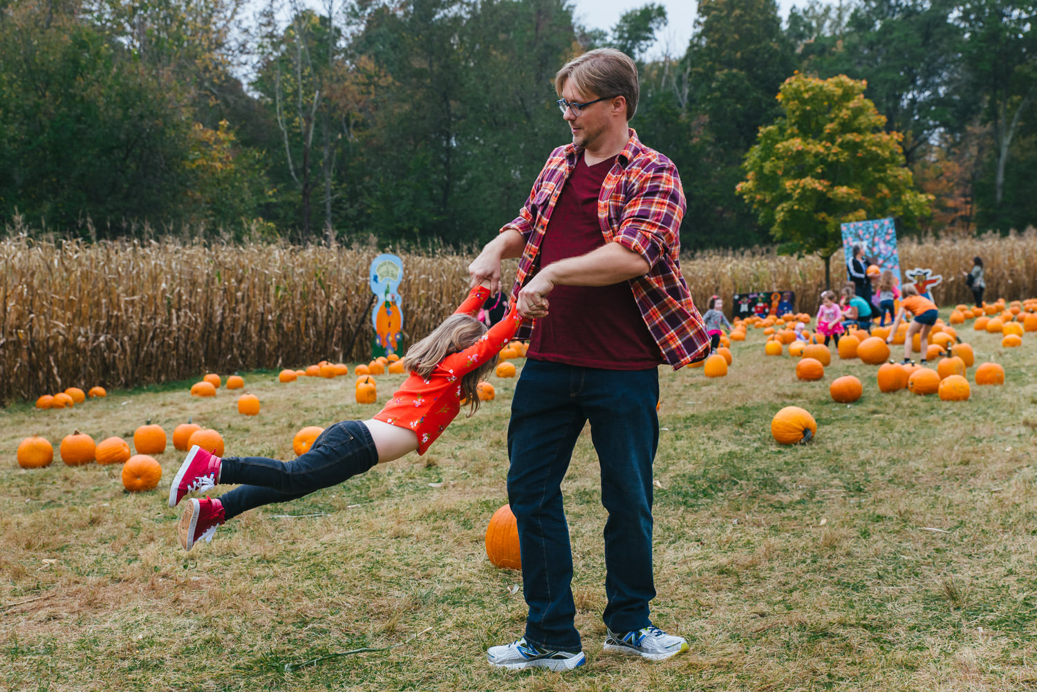 A man swings his daughter around in a pumpkin patch.