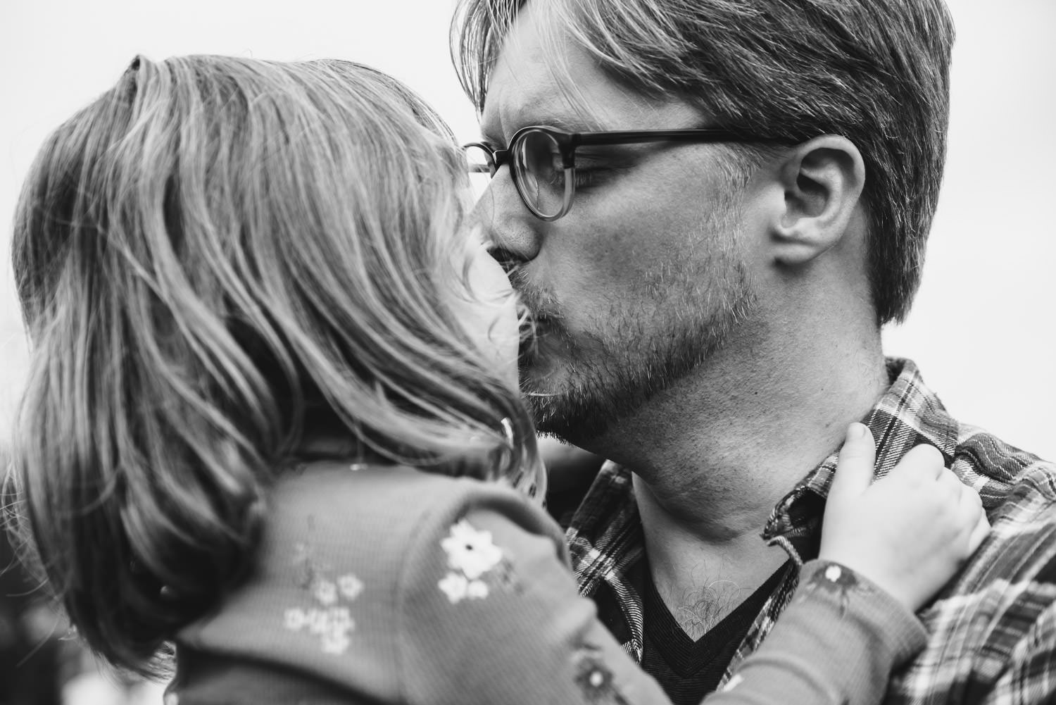 A father kisses his young daughter.