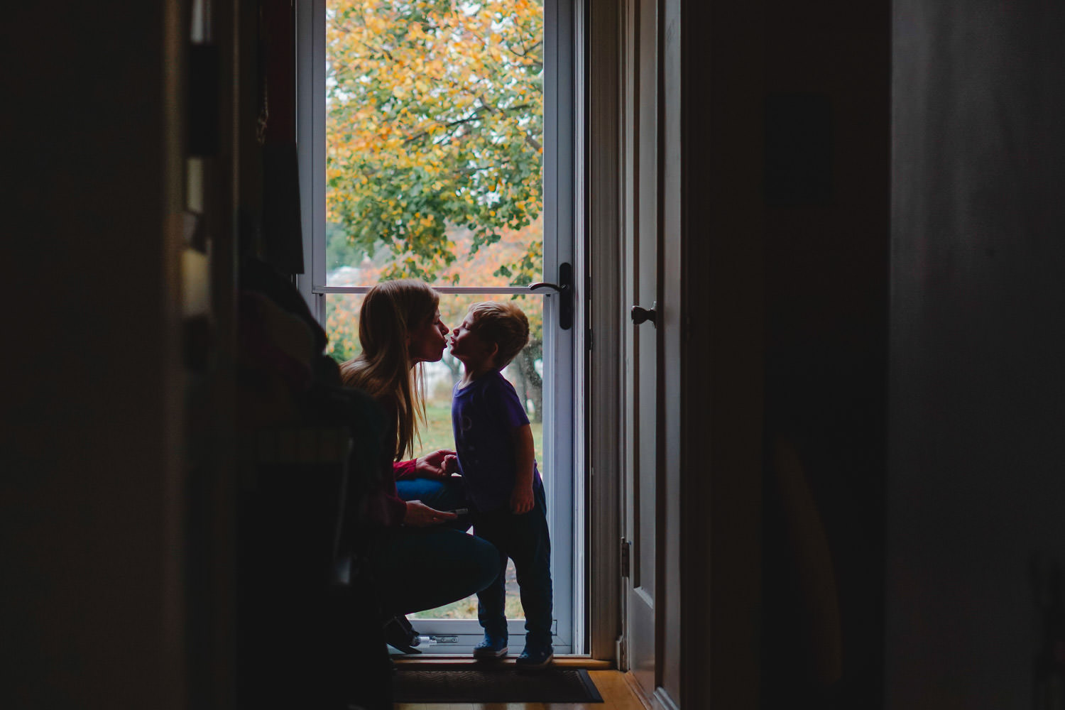 A mother kisses her son in front of a glass storm door.