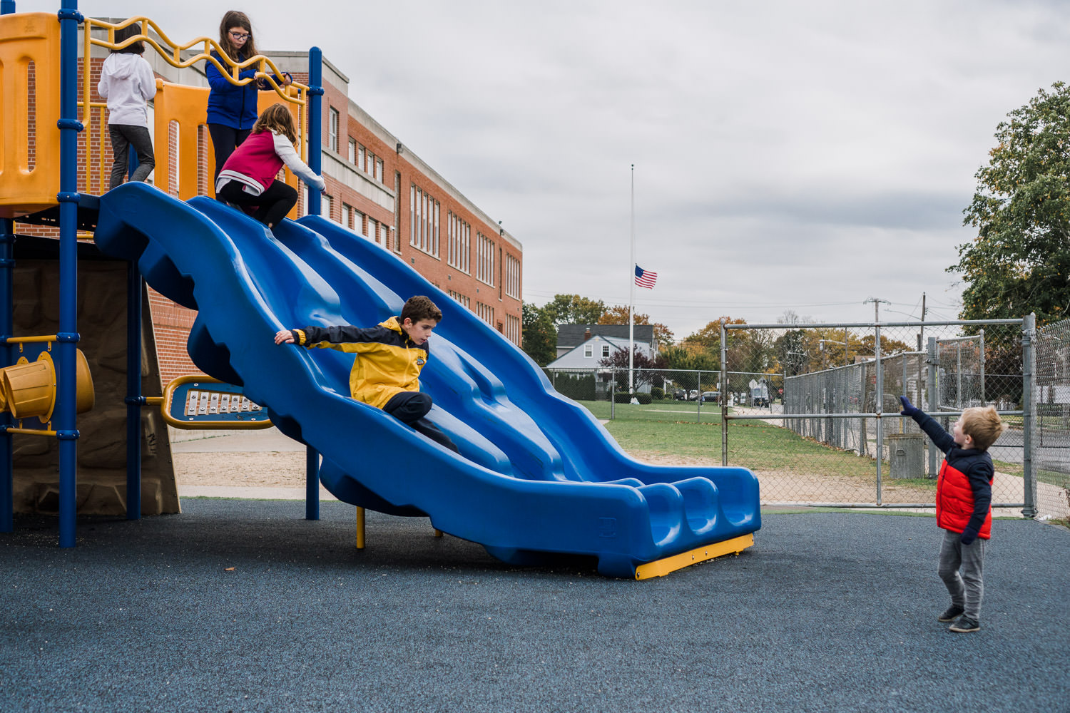 A little boy yells to some big kids at the top of a slide.