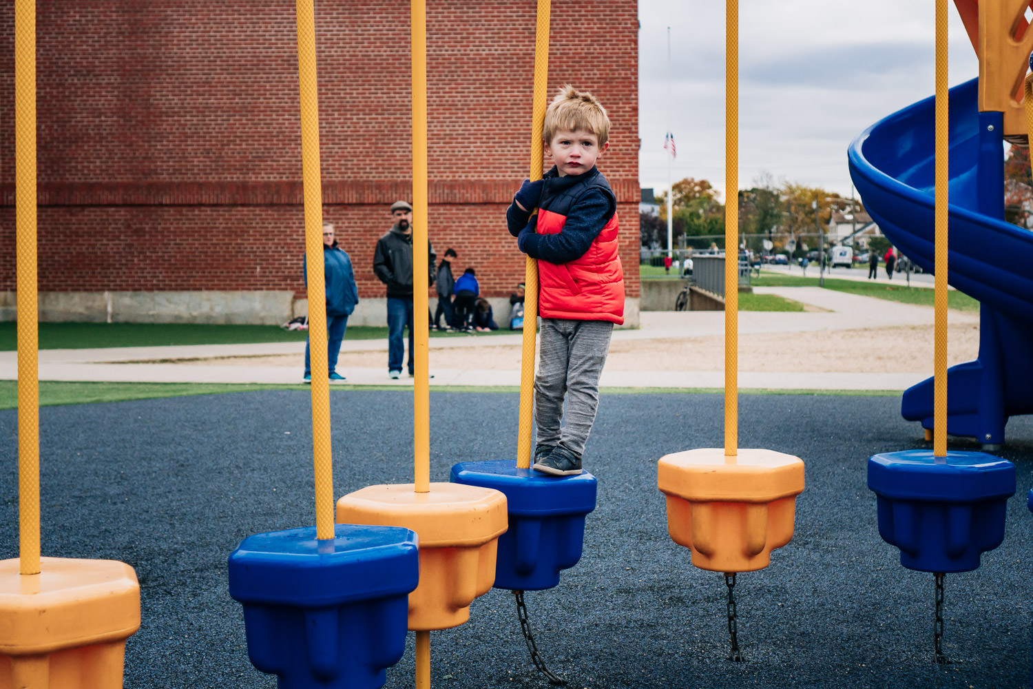 A little boy plays on a playground structure.