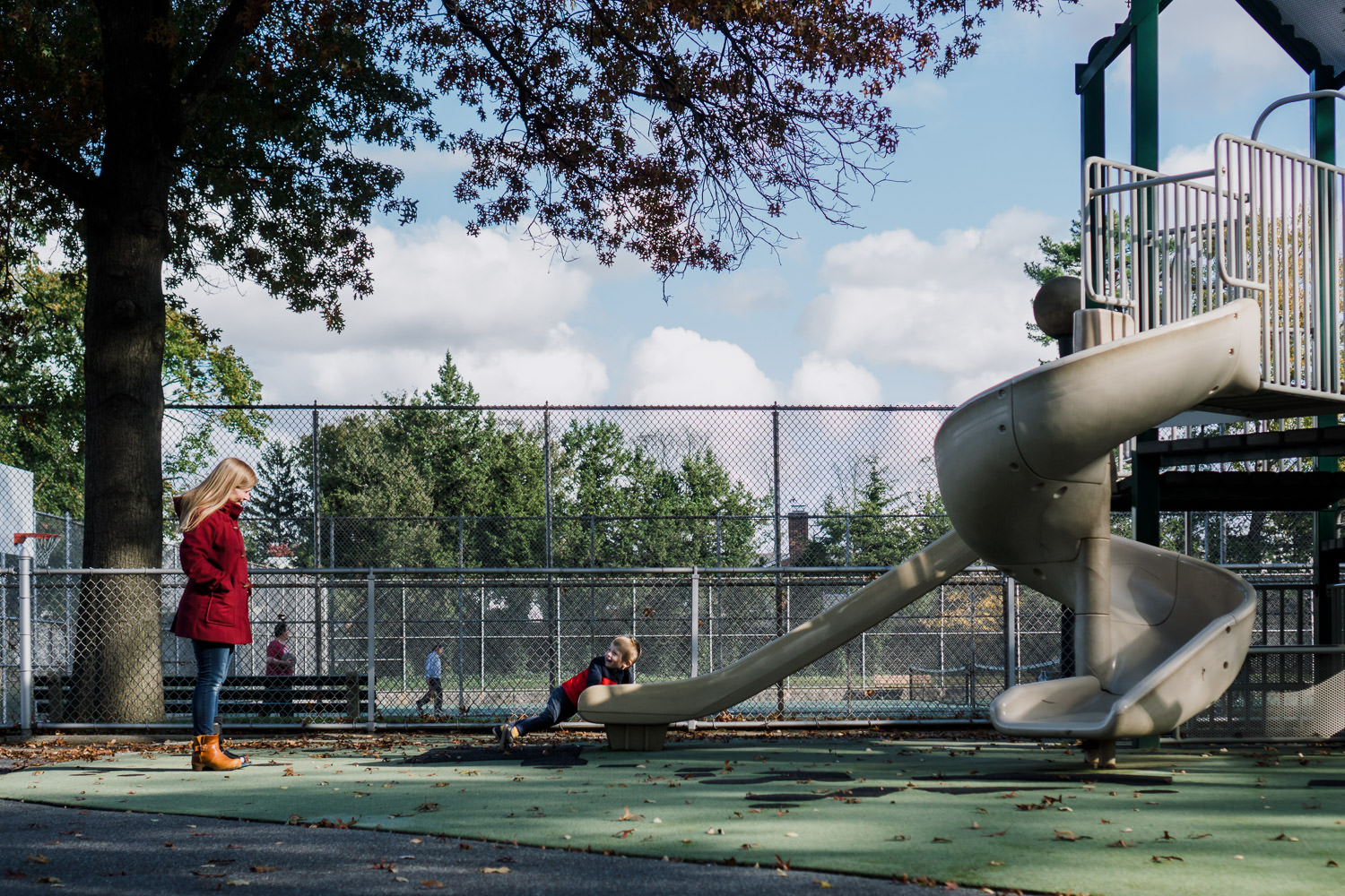 A mother watches her son come down the slide at the playground.