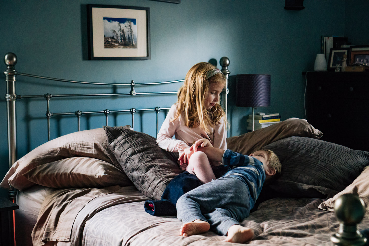 A brother and sister play on their parents' bed.