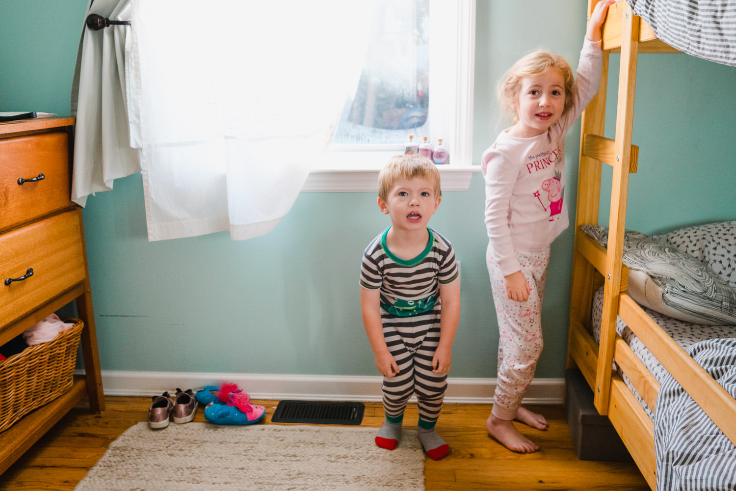 Two young siblings in pajamas stand next to their bunkbed.