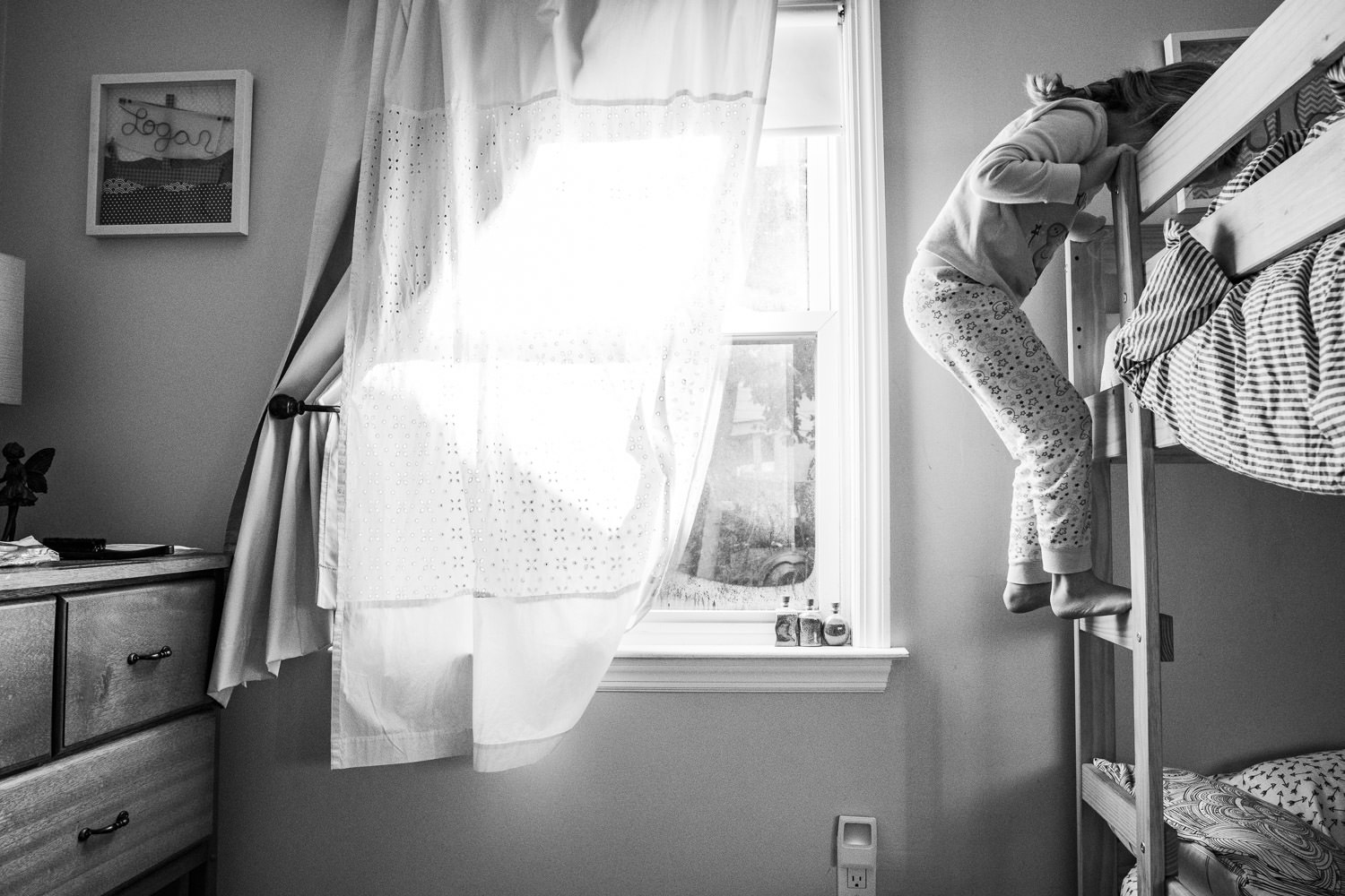 A little girl climbs up the ladder of her bunkbed.