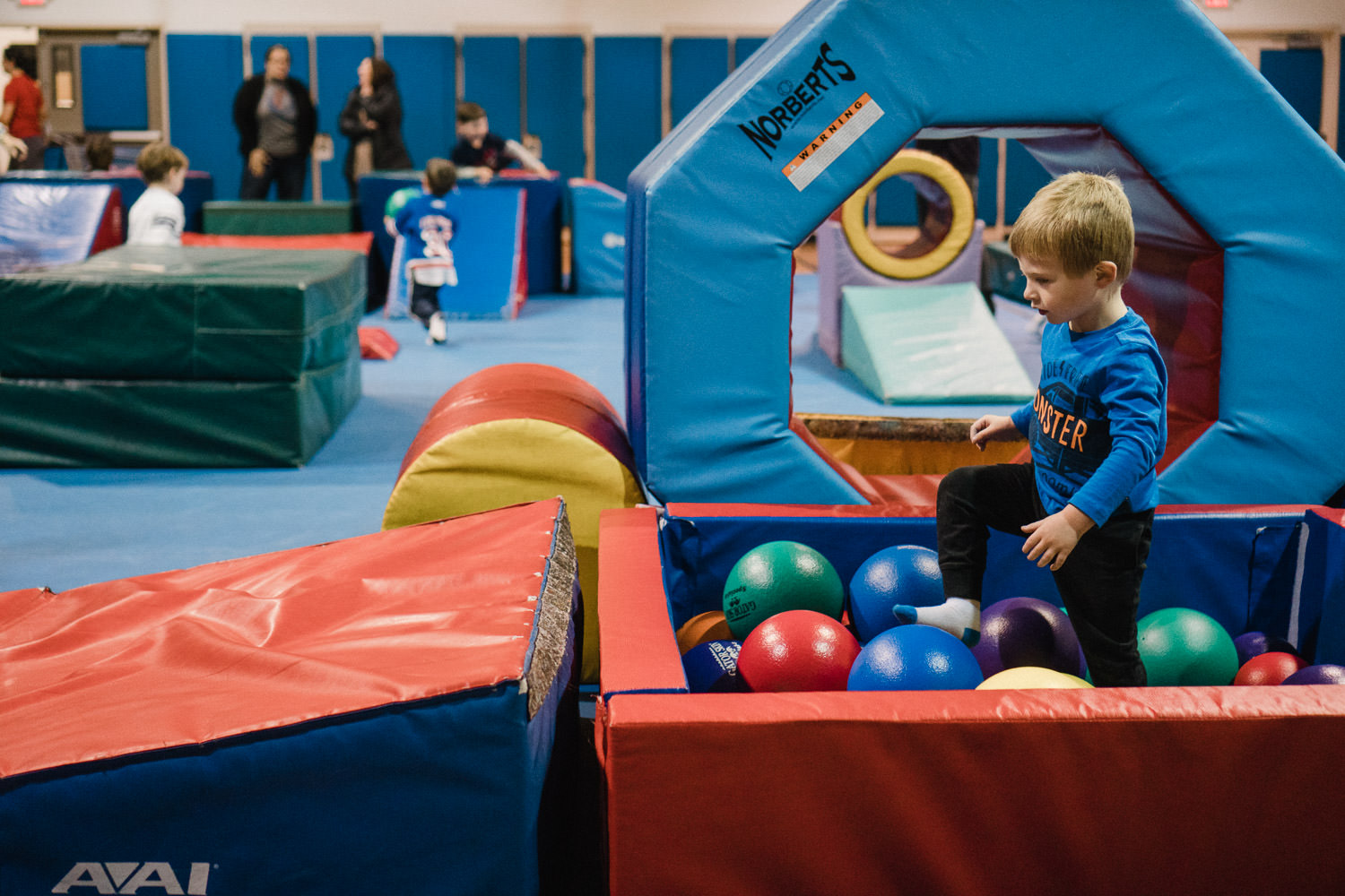 A little boy plays in a ball pit at a gym.