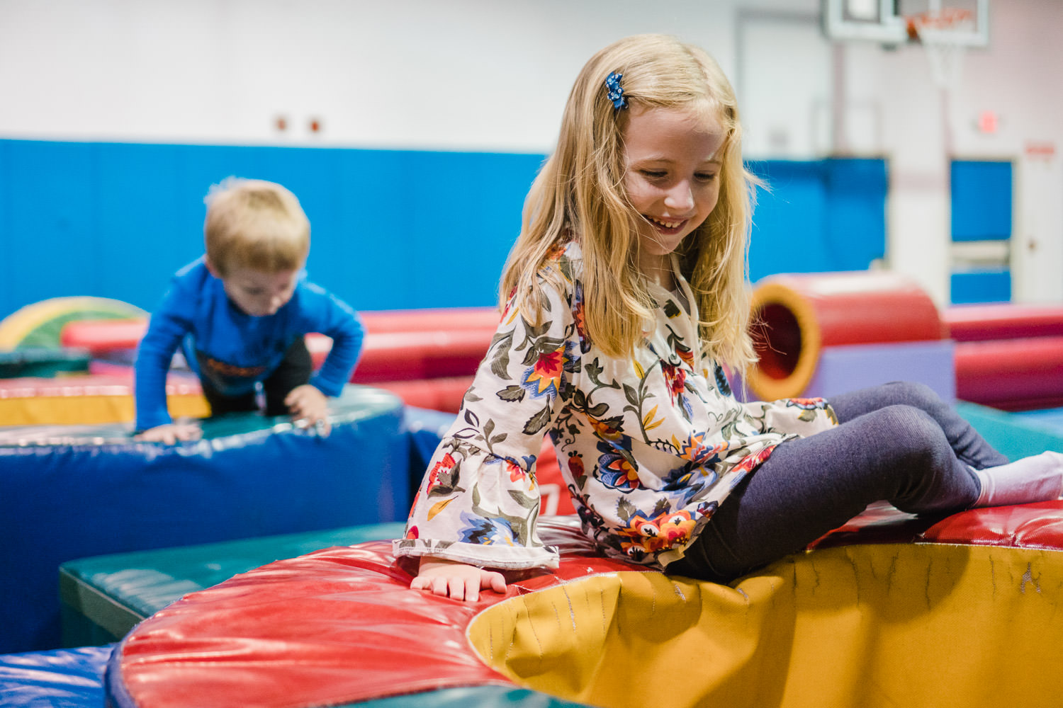 Kids play in a tumble gym.