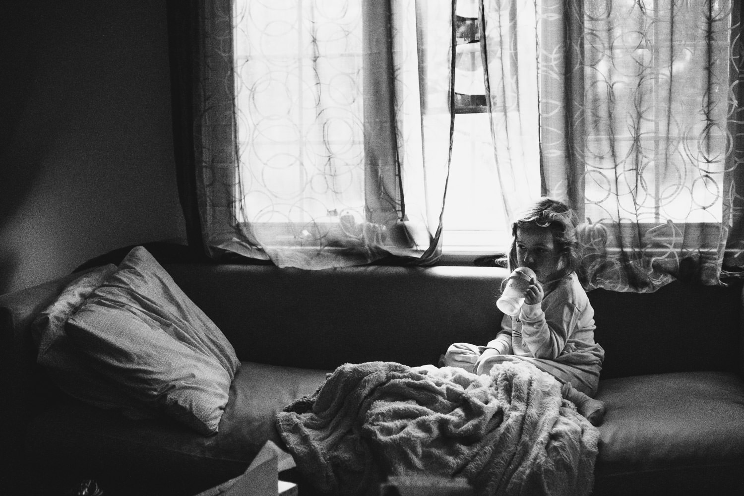 A little girl sits with a blanket on the couch.