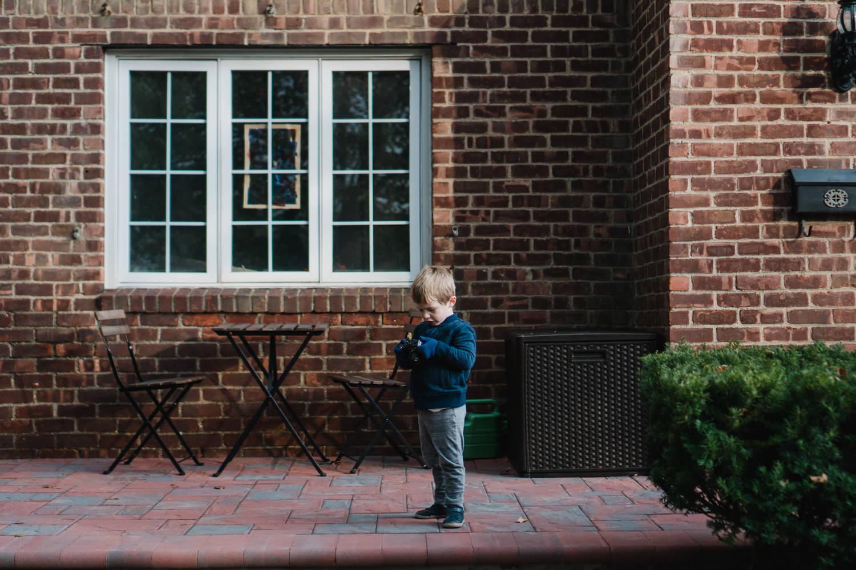Little boy standing on a porch.