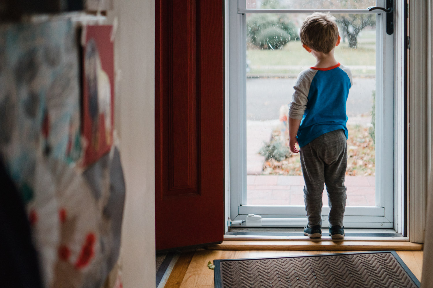 A little boy looks out the storm door to the street.