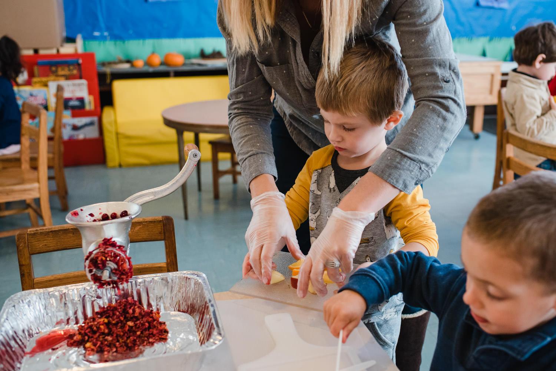 Nursery school children make cranberry relish.