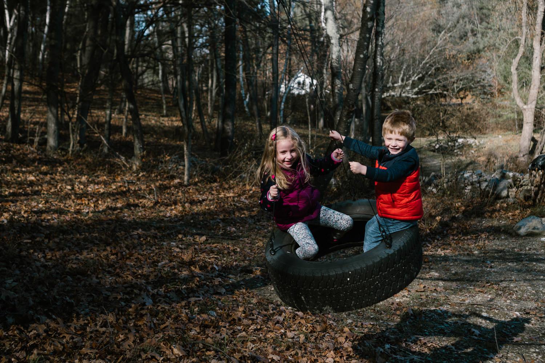 Two children swing on a tire swing.