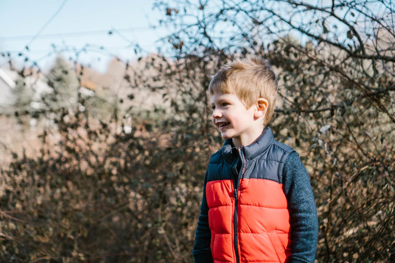 A portrait of a little boy in an orange vest.