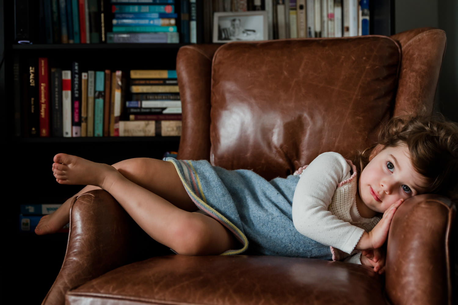 A little girl rests in a leather armchair.