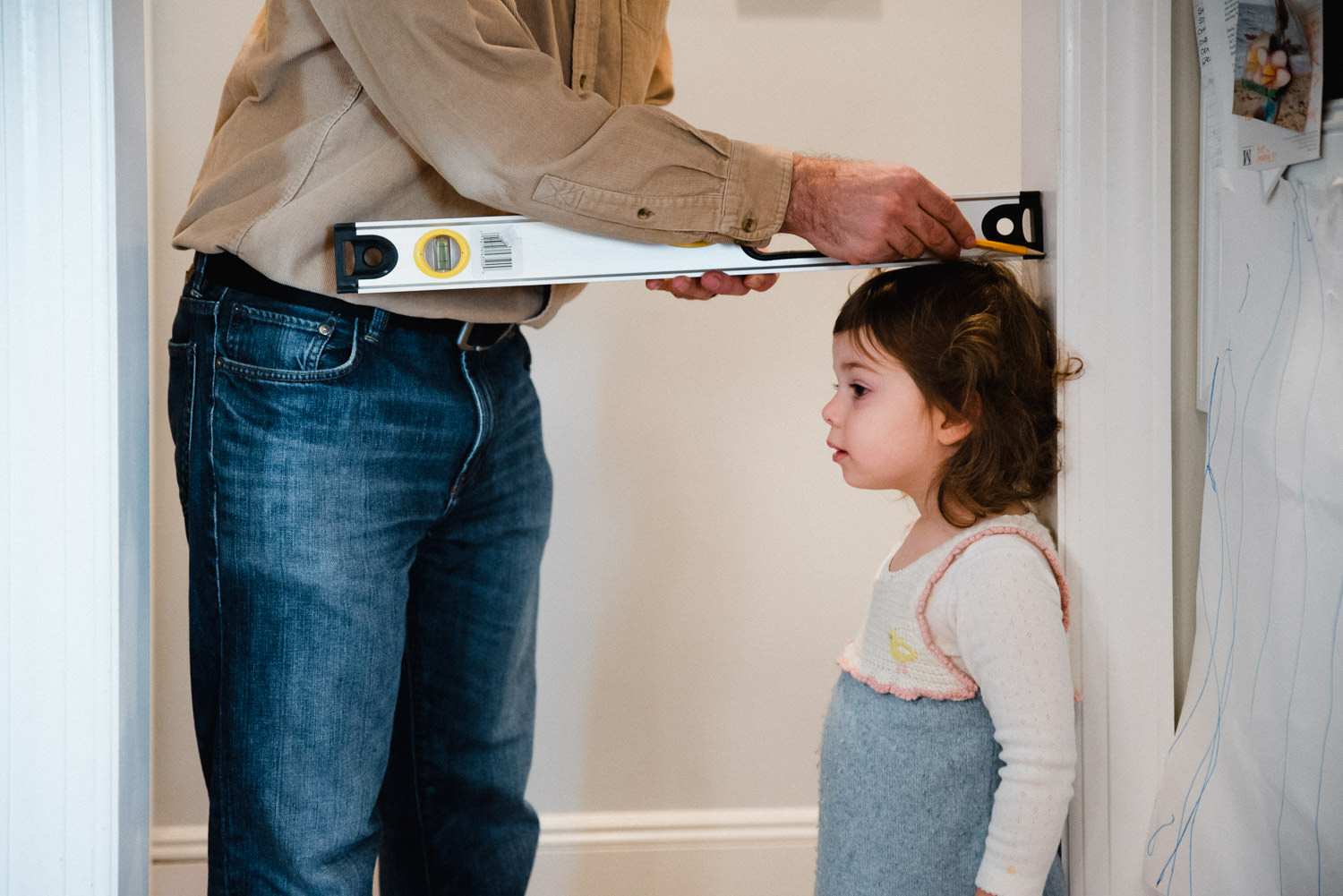 A father measures his toddler daughter.