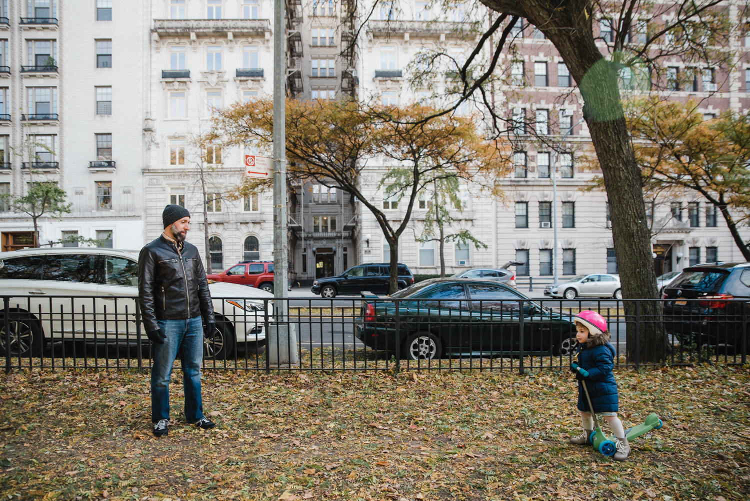 A father and daughter walk through leaves in front of some apartment buildings.