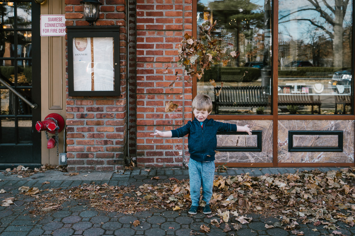 A little boy throws leaves above his head in front of a store on Franklin Ave.