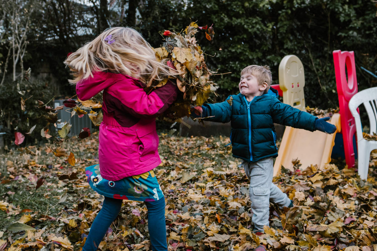 Two children have a leaf fight in their backyard.