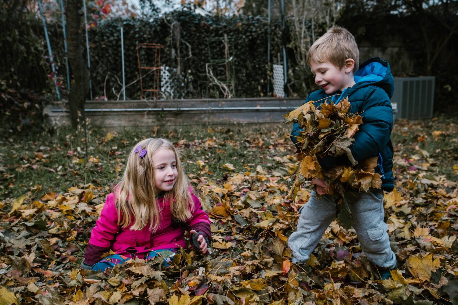 Two children play with leaves in their backyard.