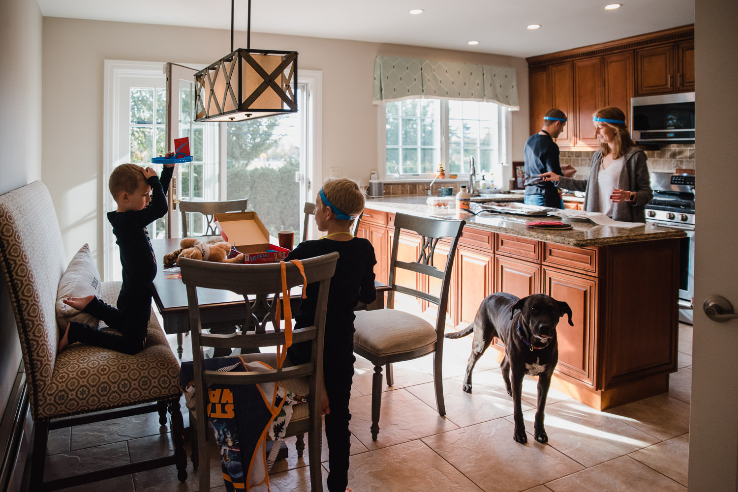 A family congregates in the kitchen to make breakfast.