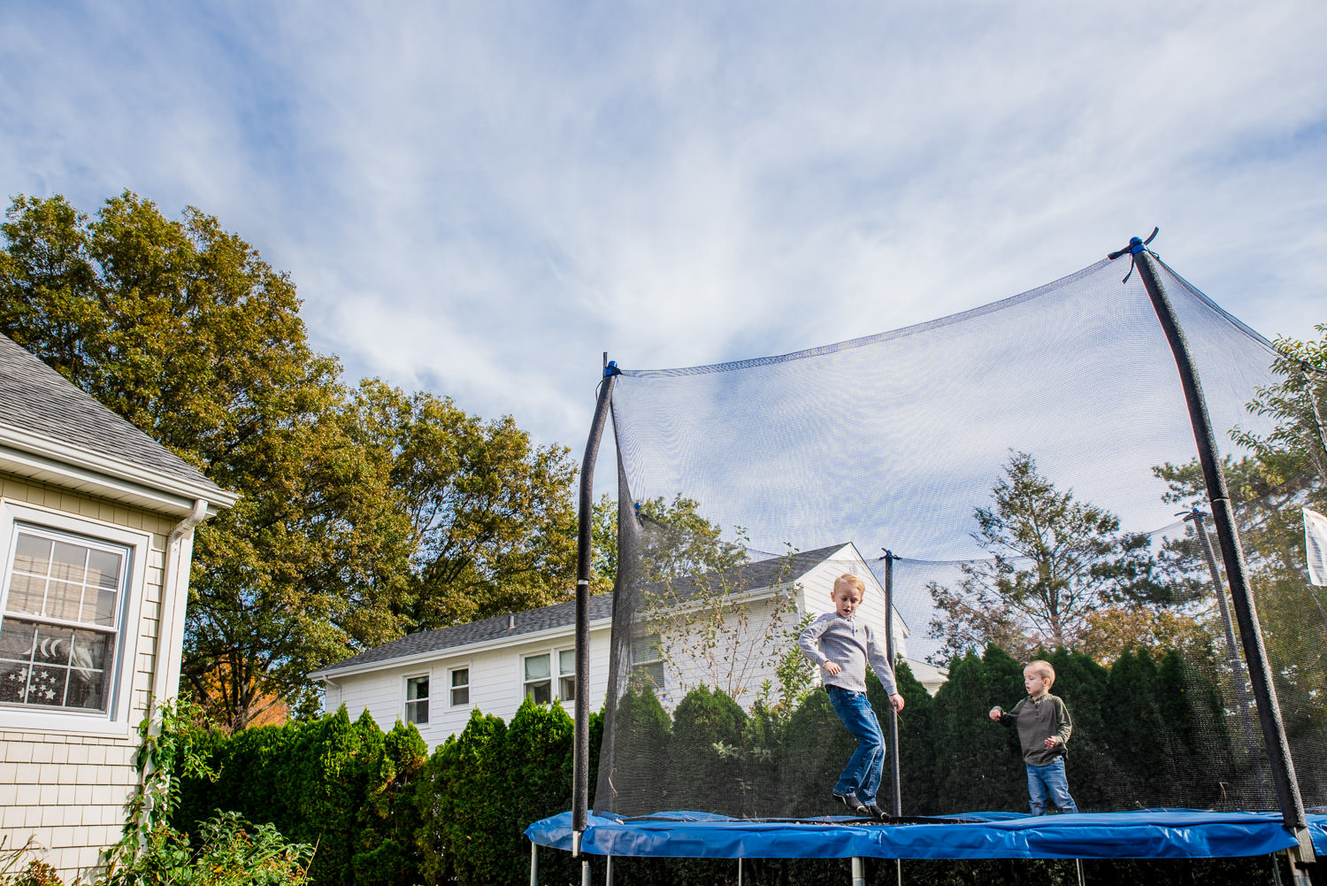 Two boys jump on a trampoline in their backyard.