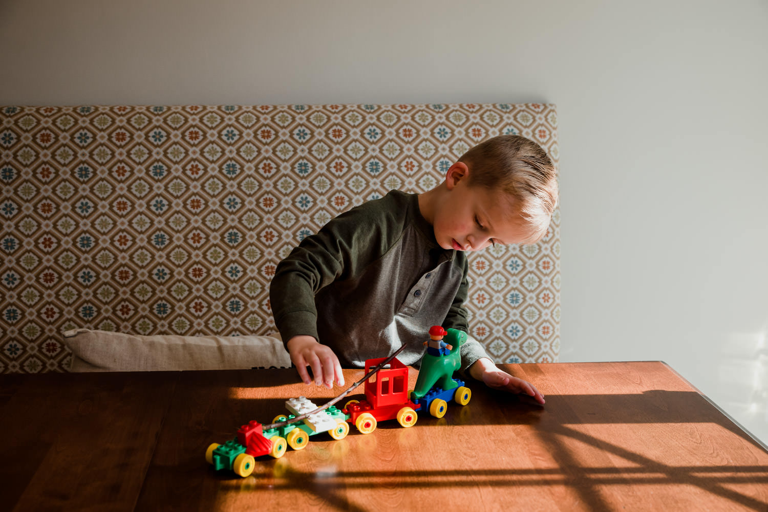 A boy plays with a lego train at the table.