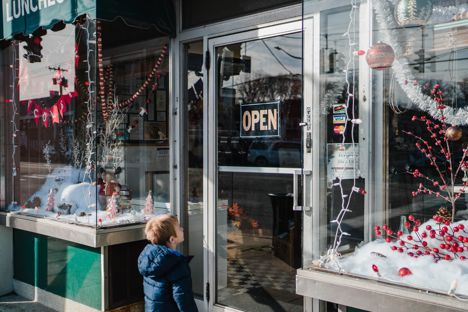 A little boy looks in a store window decorated for the holidays.