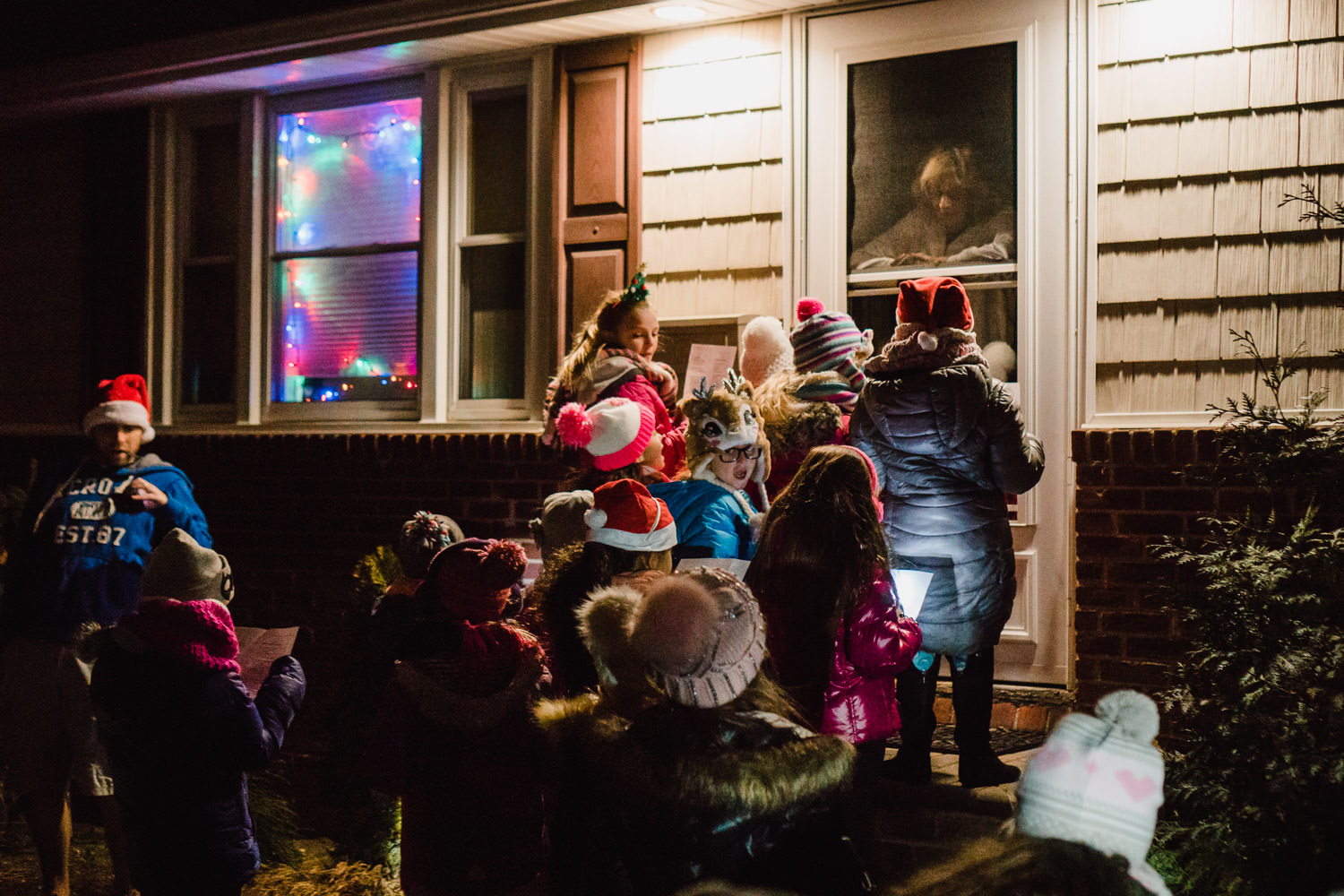 A girl scout troop sings Christmas carols on a front porch.