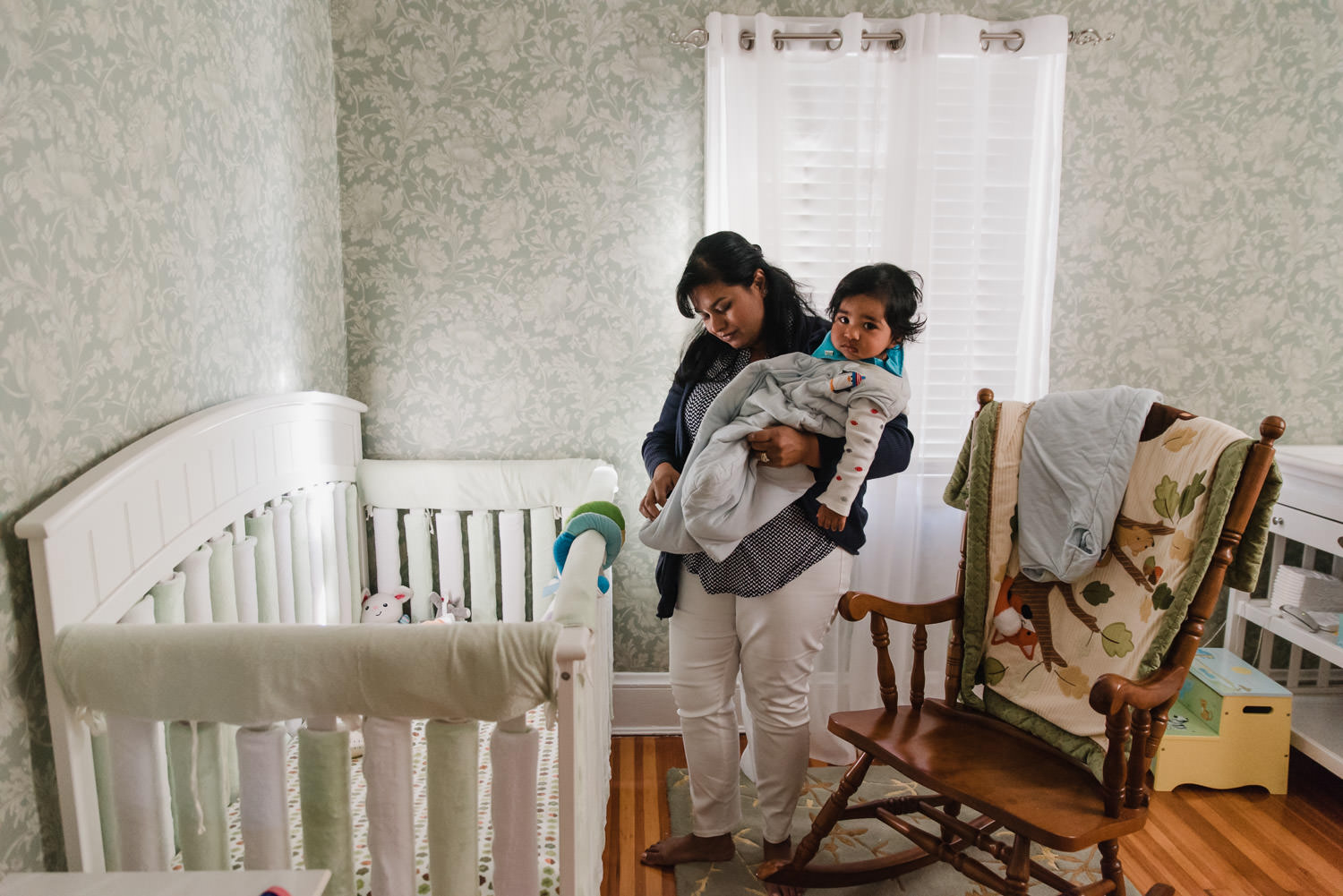 A mother holds her baby boy in his nursery.