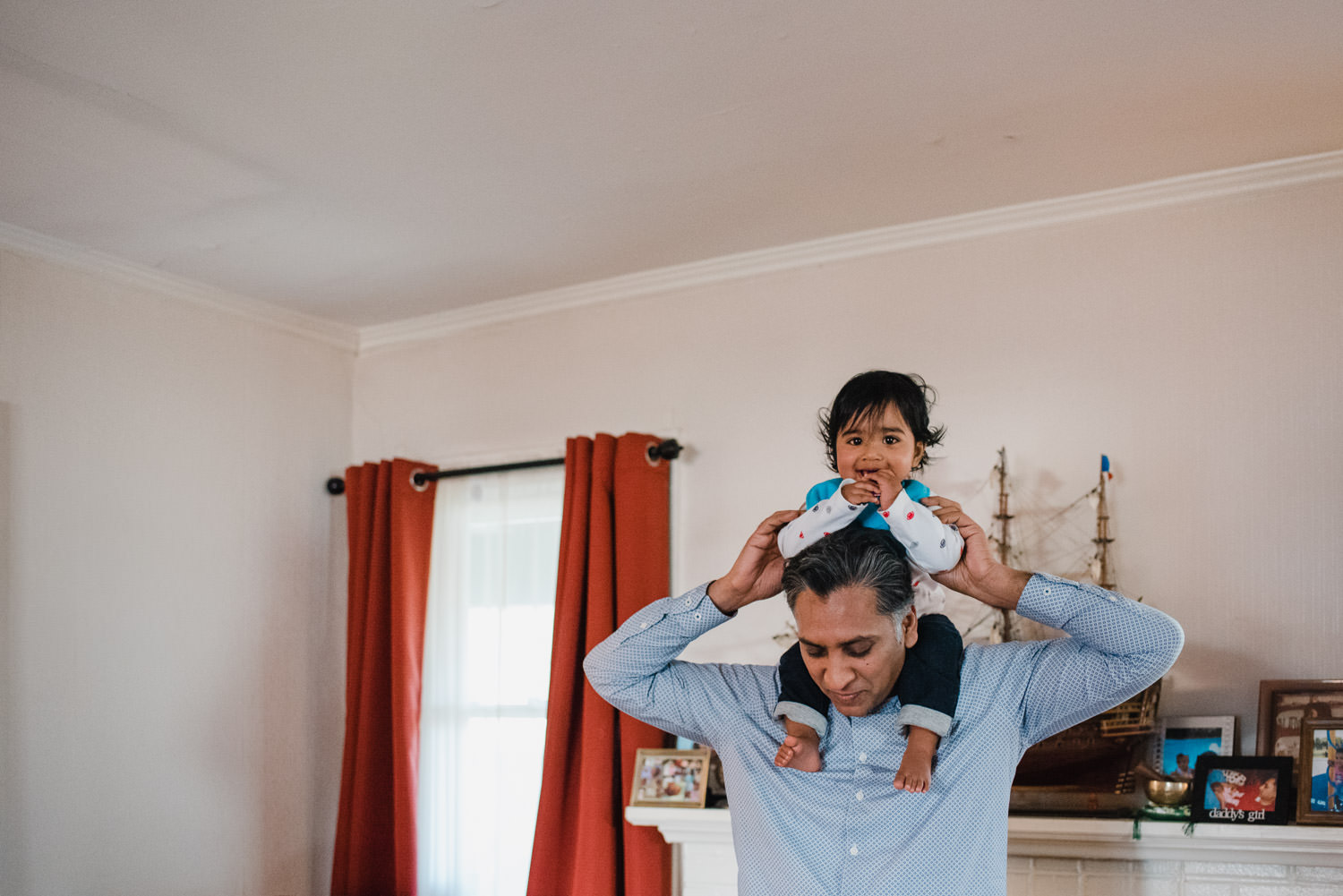 A father holds his baby son on his shoulders.