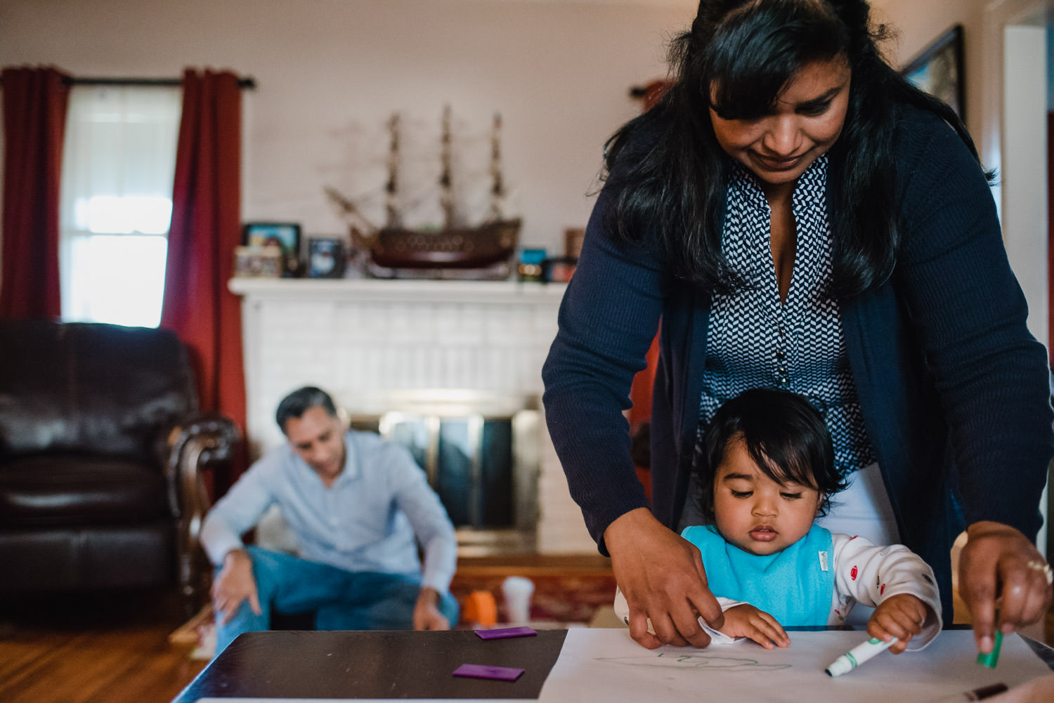 A mother helps her baby son color with markers.