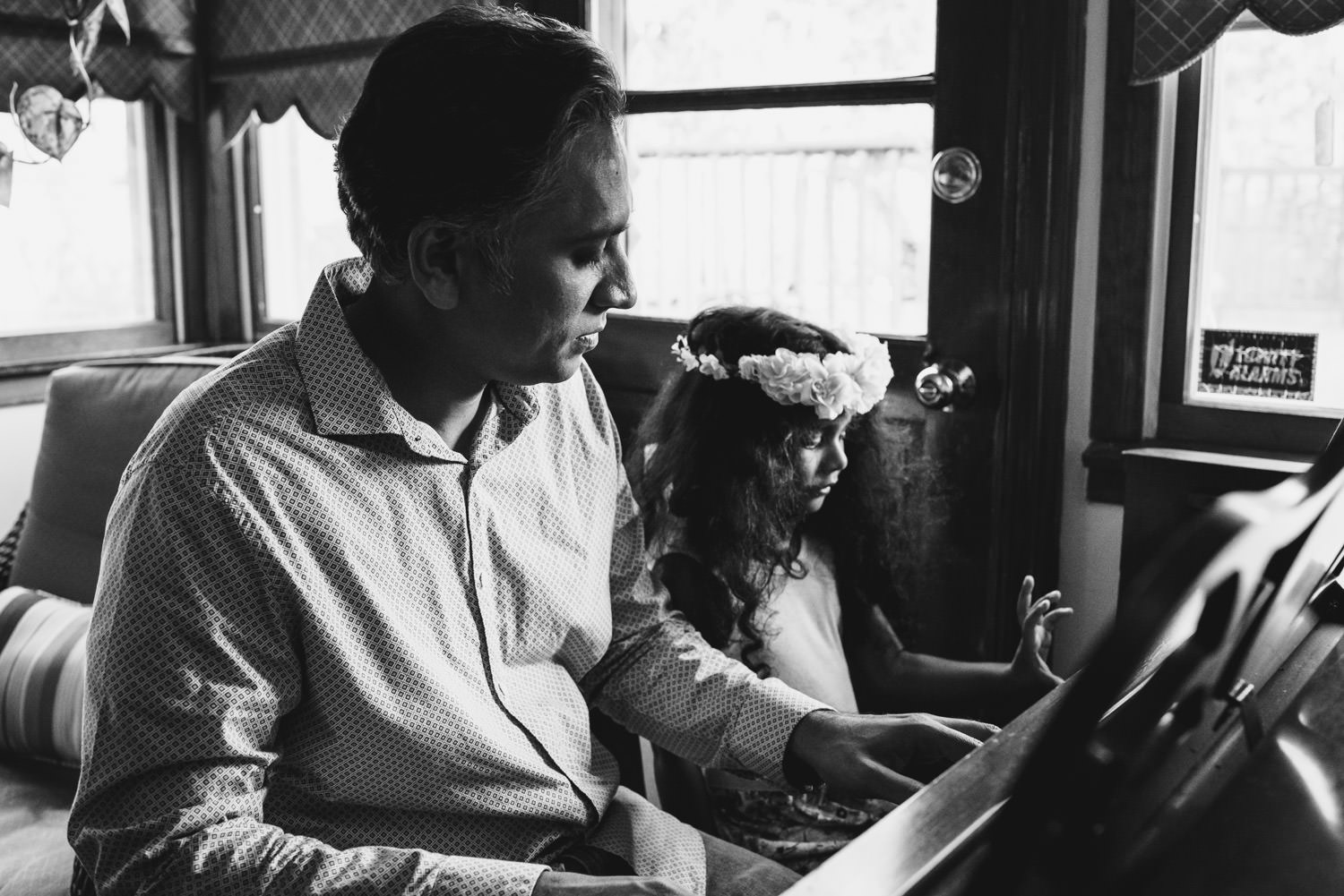 A father plays piano with his young daughter.