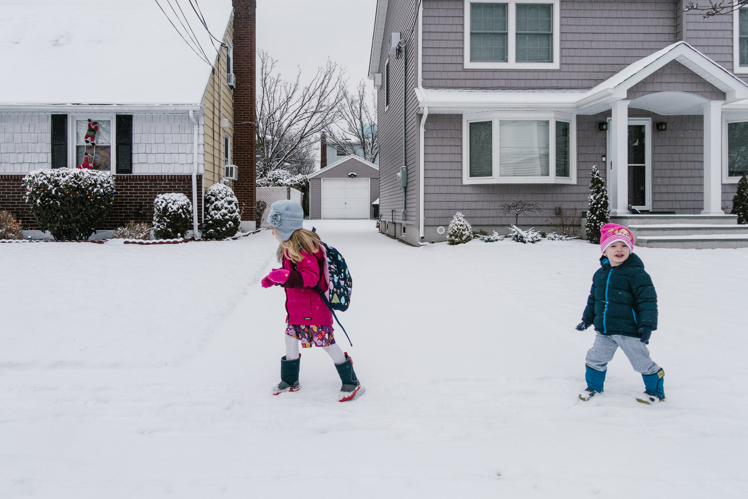 Two kids walk to school in the snow.