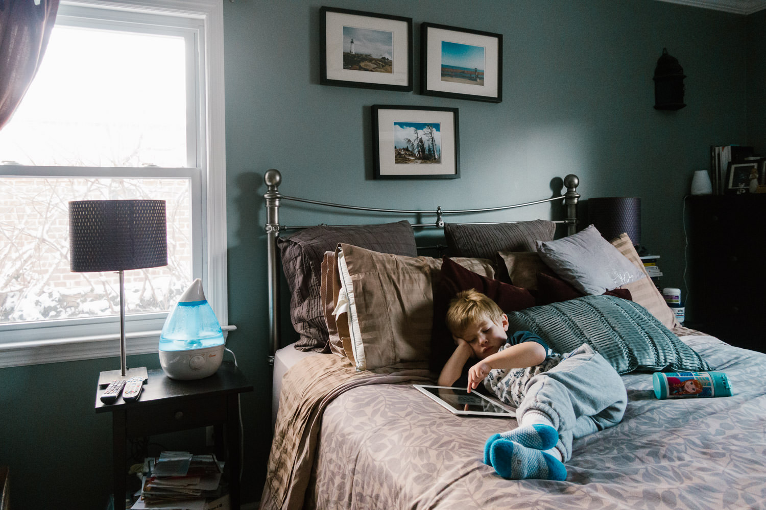 A little boy plays with an ipad on his parents' bed.