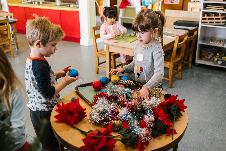 Kids decorate a Christmas tree at nursery school.