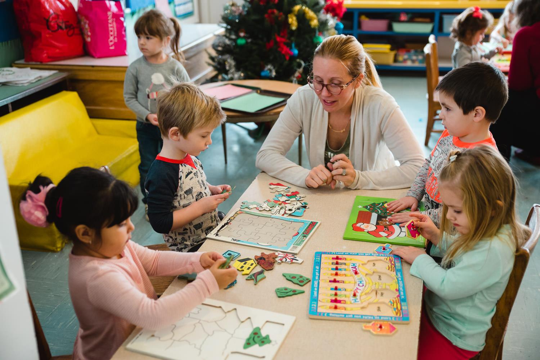 Nursery school children do puzzles.
