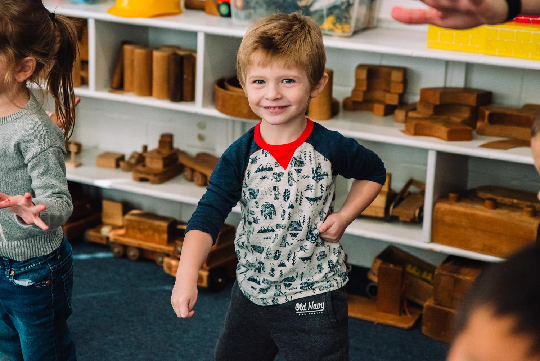 A kid dances at nursery school.