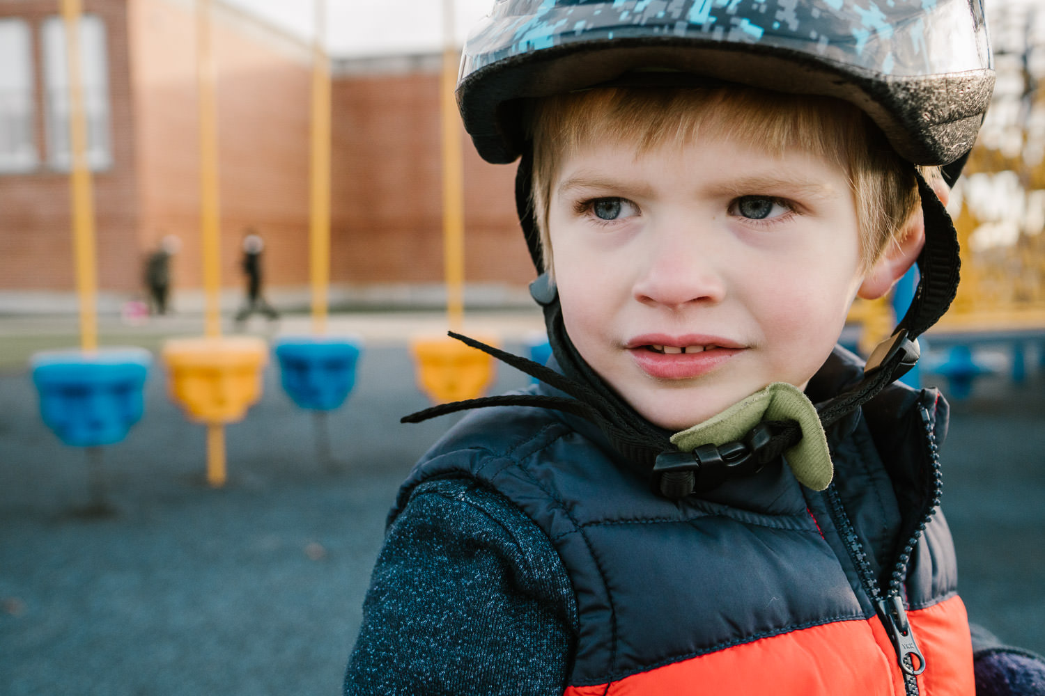 A little boy in a bike helmet at the playground.